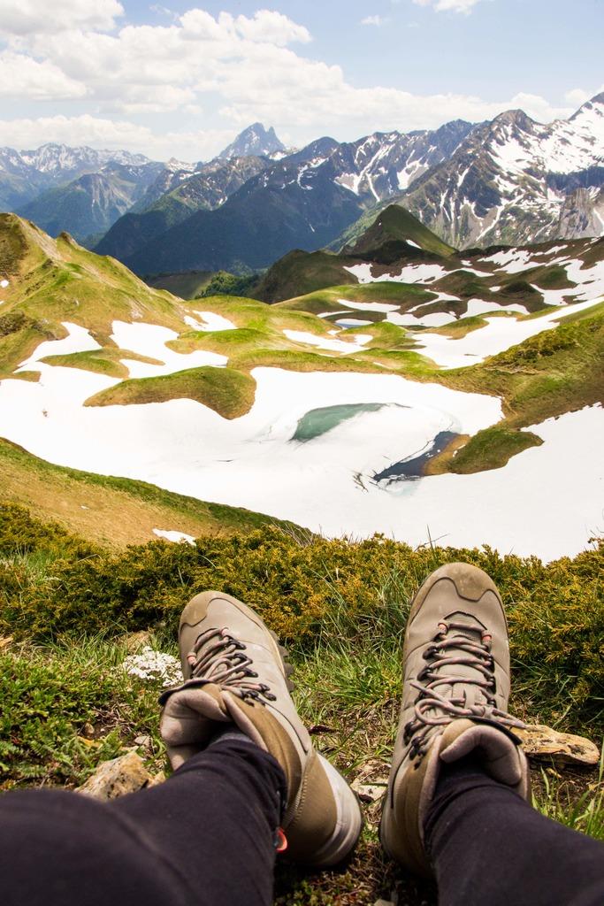 chaussures de randonnée face aux pyrénées au dessus d'un lac