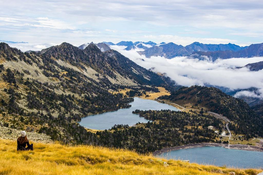 randonneur assis face aux montagnes et lacs