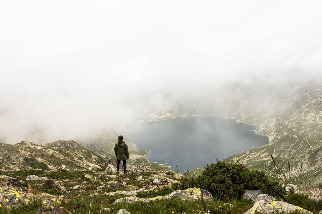 randonneur devant lac brume